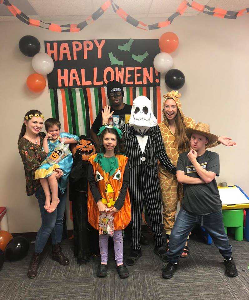Children and volunteers pose in their halloween costumes at Halloween party.
